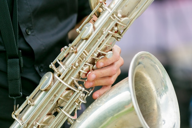 A closeup plane of saxophone in hands of sax player