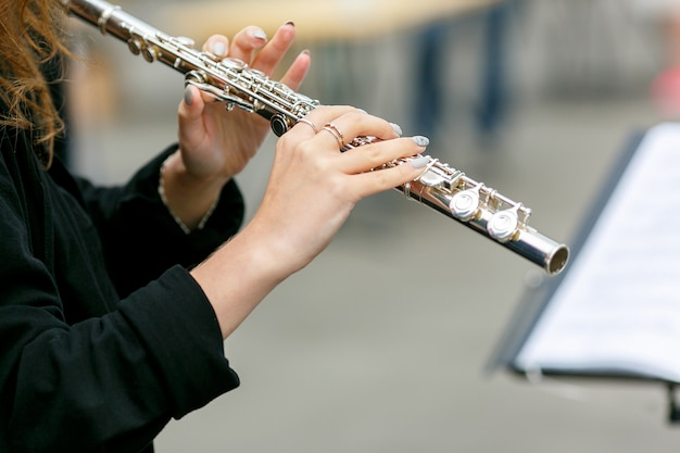 A closeup plane of street orchestra flute player