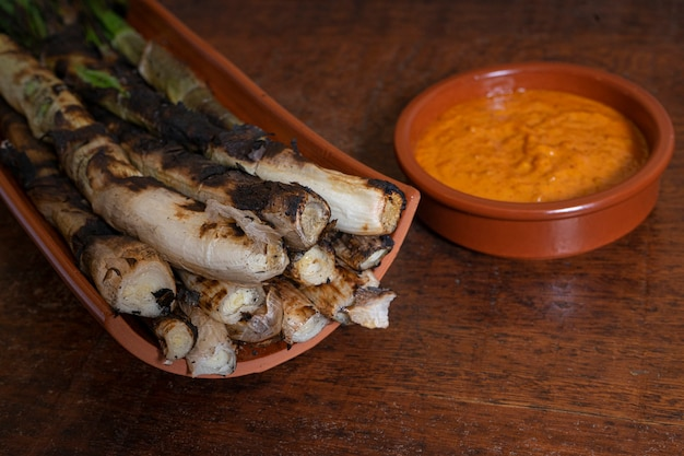 Closeup of a plate of barbecued calcots, catalan sweet onions, and a bowl with romesco sauce