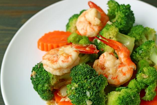 Closeup a plate of prawn stir fried with broccoli garlic and carrot