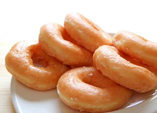 Closeup a plate of sugar-glazed doughnuts with copy space