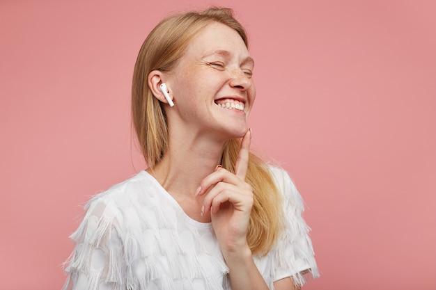 Primo piano della bella giovane bella donna rossa con acconciatura casual che ride felicemente con gli occhi chiusi mentre si ascolta la musica nei suoi auricolari, isolato su sfondo rosa