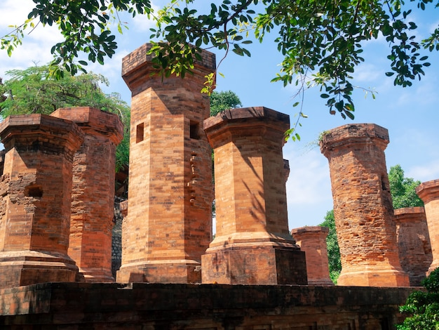 Closeup po nagar cham tower stone sticks, ancient temple at nha trang, vietnam in shady of green trees with cloudy blue sky