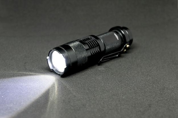 Closeup pocket led flashlight on dark background.
