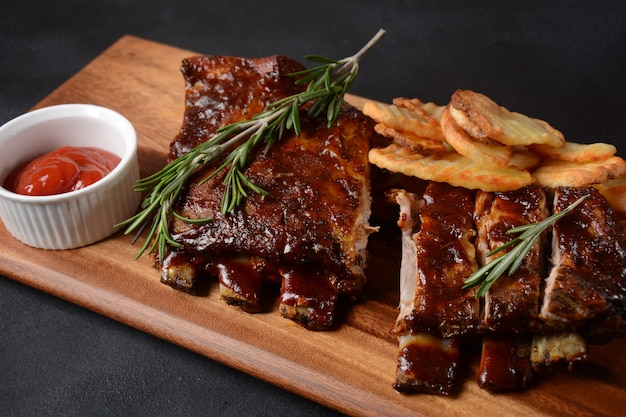 Closeup of pork ribs grilled with bbq sauce and caramelized in honey. tasty snack to beer on a wooden board. grilled pork ribs with spices on a stone background