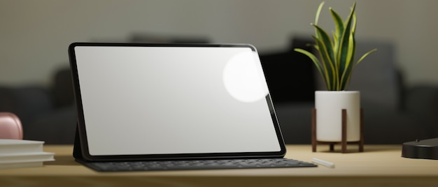Closeup portable tablet computer blank screen mockup with keyboard stand on work table under light
