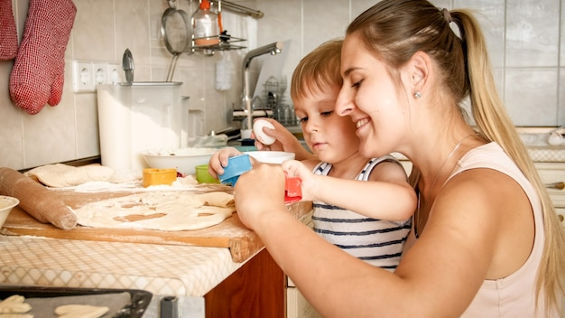 Closeup portrait of adorable 3 years old toddler boy making cookies with mother
