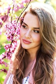 クローズアップの肖像画屋外の日光の下で長い髪の驚くべき陽気な若い女性