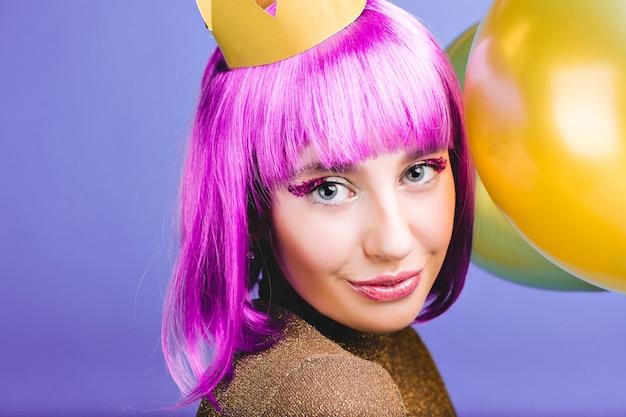 紫色の髪をカット、黄金の王冠、カーニバル、新年パーティーを祝う風船を持つ驚くべきうれしそうな若い女性のクローズアップの肖像画。魅力的な笑顔、ティンセルのメイク、幸せ。