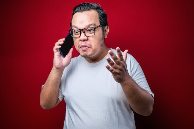 Closeup portrait angry young asian man, guy mad student, pissed off employee shouting while on phone isolated red background. negative human emotion face expression feeling attitude