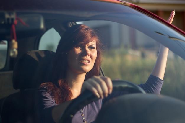 クローズアップの肖像画、彼女の前でドライバーに腹を立て、手で身振りで示す怒っている若い座っている女性。ロードレイジ交通渋滞の概念