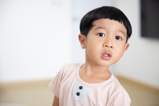 クローズアップの肖像画アジアの子供男の子ストレート黒髪カメラを見て薄茶色のシャツを着て