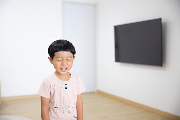クローズアップの肖像画アジアの子供男の子ストレート黒髪の薄茶色のシャツを着て探しています