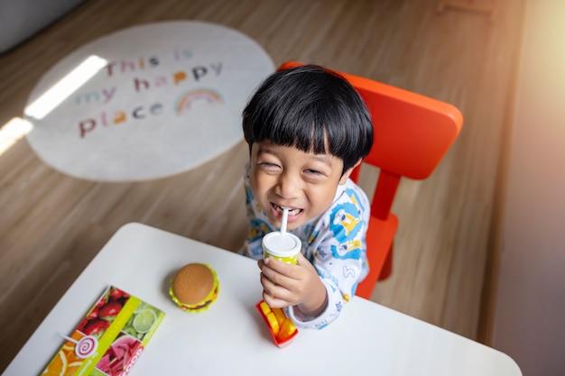 クローズアップの肖像画アジアの子供男の子ストレート黒髪の白いパジャマを着てカメラを見て
