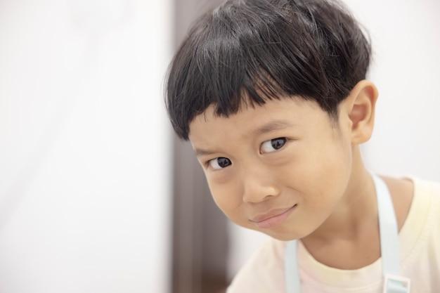 クローズアップの肖像画アジアの子供男の子ストレート黒髪の白いシャツを着てカメラを見て