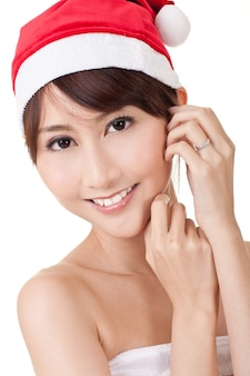 Closeup portrait of asian christmas lady smiling and looking at you on white wall..