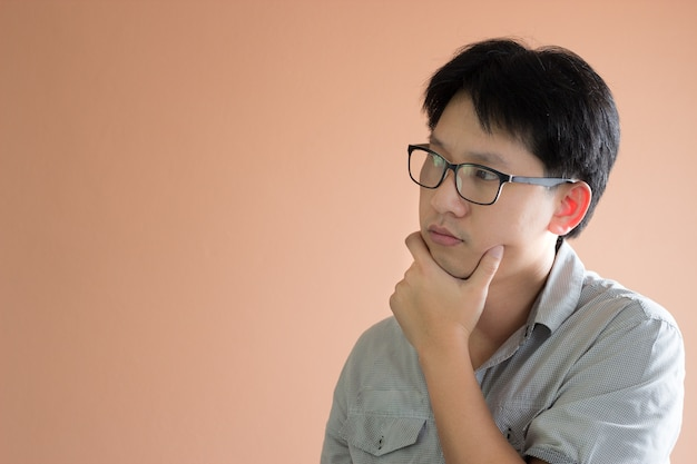 Closeup portrait asian man with chin on the hand look like thinking  something,