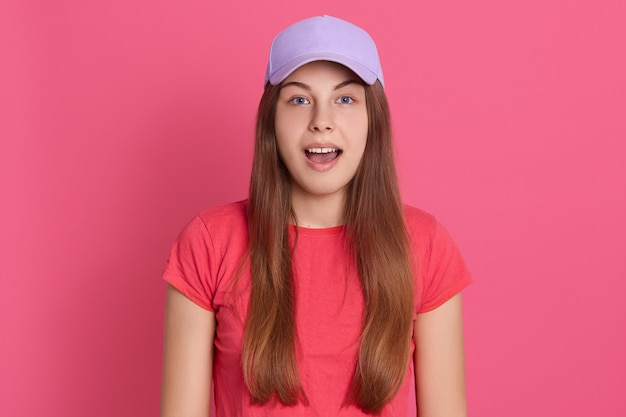 Closeup portrait of astonished female wearing red t shirt and baseball cap, keeps mouth opened, looks surprised