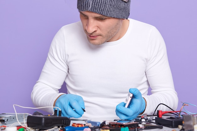 Closeup portrait of attentive well skilled electronic engineer doing repair