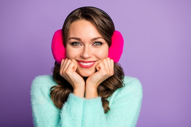 Closeup portrait of attractive funny lady arms on cheekbones enjoy good weather look window toothy smiling wear fuzzy pastel pullover pink warm ear covers.
