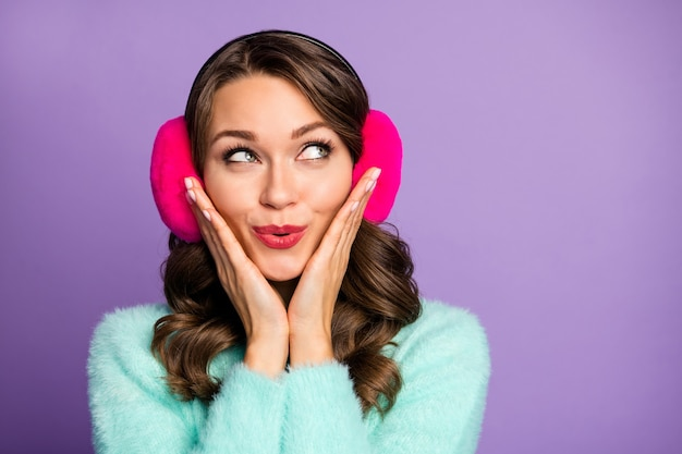 Closeup portrait of attractive funny lady look side empty space arms on cheekbones black friday advert wear fuzzy pastel pullover pink warm ear covers.