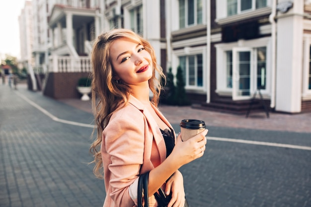 Closeup portrait  attractive model with vinous lips walking with coffee in coral jacket on street.