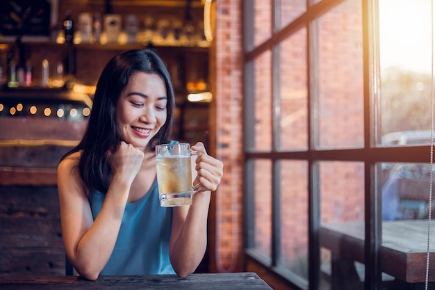 Closeup portrait, attractive woman enjoying drinking beer inside bar.