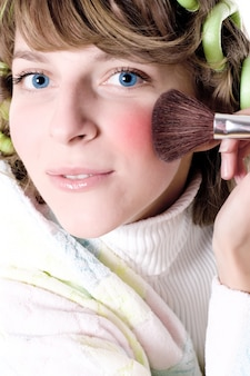 Closeup portrait of attractive young woman applying make-up