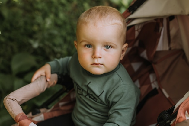 Closeup portrait of a baby boy in a green sweater sitting in a stroller. high quality photo