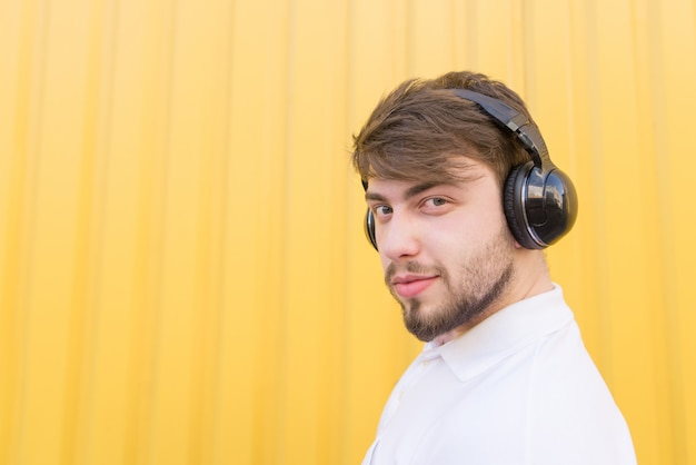 Closeup portrait of a bearded man in wireless headphones on a yellow wall.