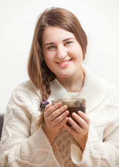 Closeup portrait of beautiful brunette woman holding big cup of tea