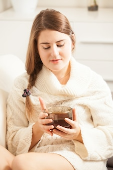 Closeup portrait of beautiful brunette woman lying on sofa and holding cup of tea