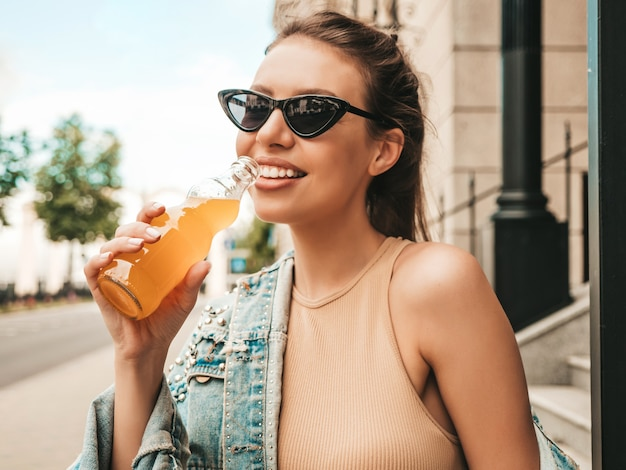 Closeup ritratto di bella modella carina in vestiti di giacca di jeans hipster estivi in posa in strada