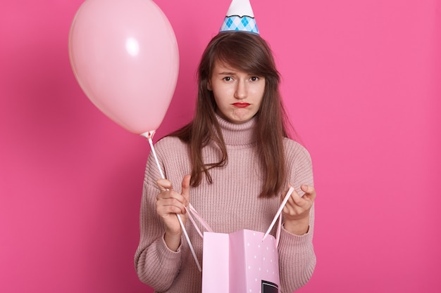 Closeup portrait of beautiful disappointed girl with gift package and balloon