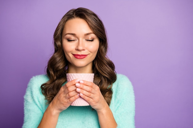 Closeup portrait of beautiful dreamer lady holding hot coffee beverage cup eyes closed enjoy nice smell emotional wear pastel fuzzy sweater.