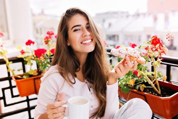Bella ragazza del ritratto del primo piano con capelli lunghi che fa colazione sul balcone la mattina in città. tiene una tazza, un croissant, sorridendo.