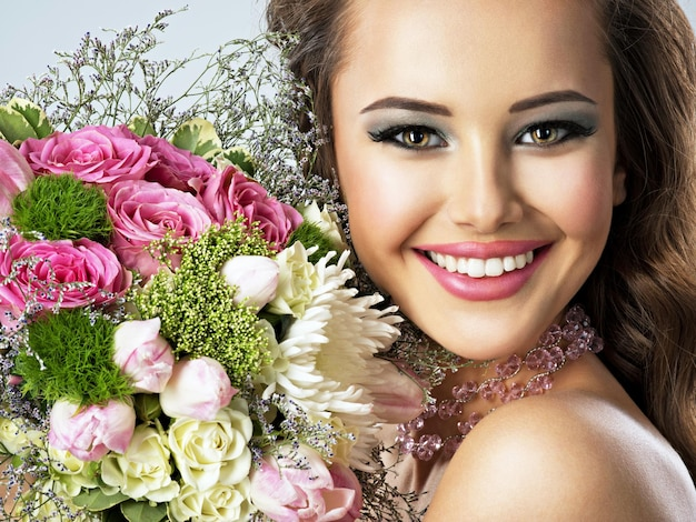 Closeup portrait of beautiful happy girl with flowers in hands. young attractive woman holds the bouquet of spring flowers