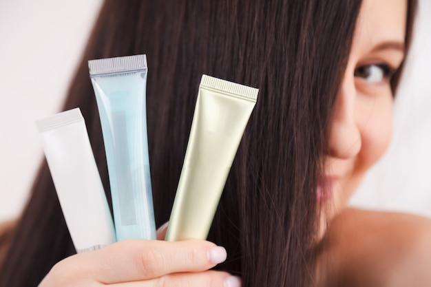 Closeup portrait beautiful long hair young girl holding skincare cosmetics, tubes with face cream, body mask, serum, lip balm.
