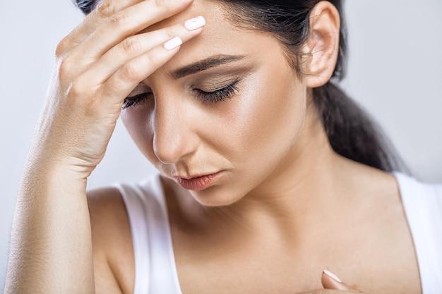 Closeup portrait of beautiful sick girl suffering from headache