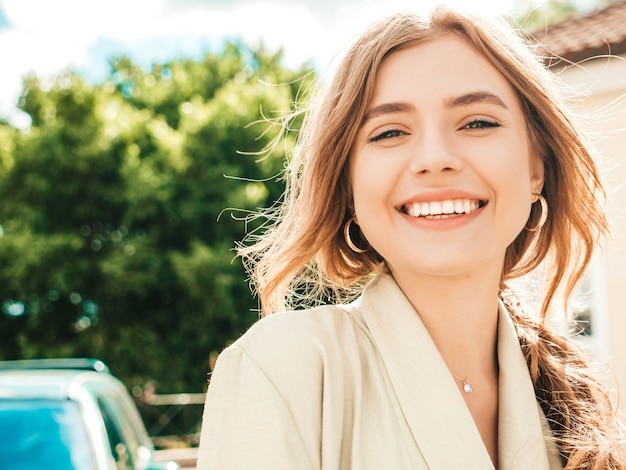 Closeup portrait of beautiful smiling blond model. trendy female posing in the street  at sunset. pretty and cheerful