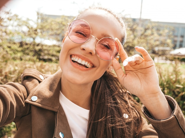 Closeup portrait of beautiful smiling brunette girl in summer hipster jacket  model taking selfie on smartphone woman making photos in warm sunny day in the street in sunglasses