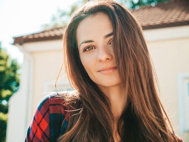 Closeup portrait of beautiful smiling brunette model. trendy female posing in the street
