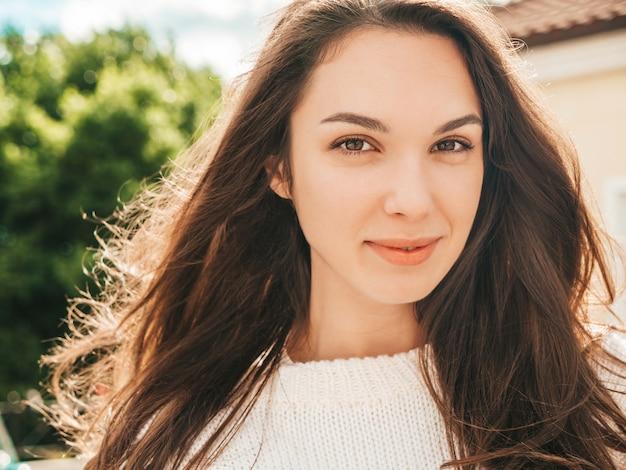 Closeup portrait of beautiful smiling brunette model. trendy girl posing in the street