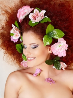 Closeup portrait of beautiful smiling redhead ginger woman face with colorful flowers in hair in porofile