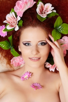 Closeup portrait of beautiful smiling redhead ginger woman face with colorful flowers in hair touching face