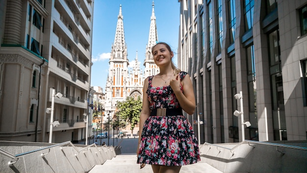 Closeup portrait of beautiful smiling young woman in sunglasses posing against modern building and old catholic cathedral in european city