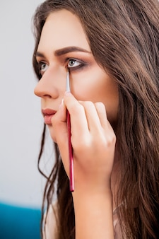 Closeup portrait of beautiful woman getting professional make-up with brush