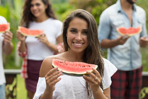 Closeup portrait of beautiful woman holding watermelon with friends happy cheerful group of people h