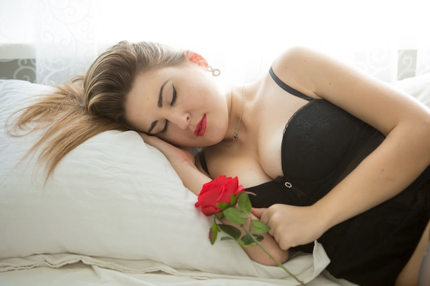Closeup portrait of beautiful woman sleeping in bed and holding red rose