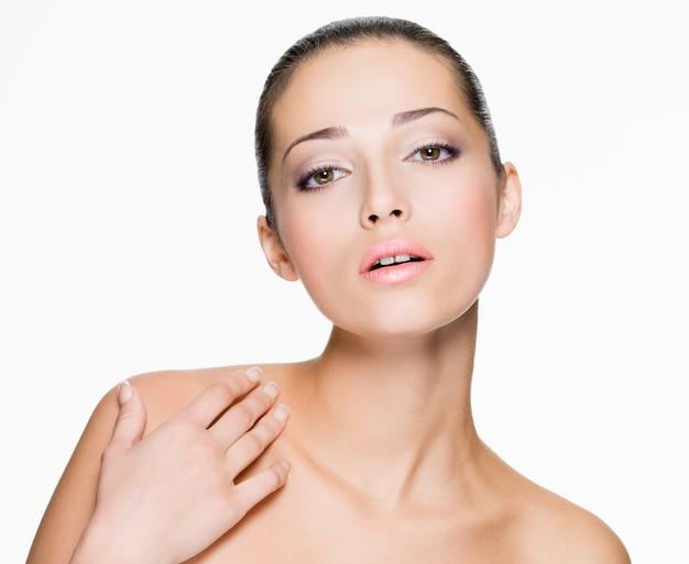 Closeup ritratto di bella donna con la pelle fresca del viso - isolato su bianco
